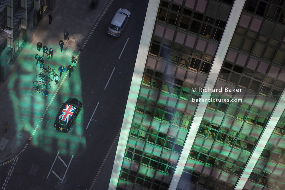 Looking down from an aerial view towards green reflected light and a passing taxi cab with a union Jack flag on its roof with passing business figures walking through the City of London, the capital's ancient financial district, on 13th May, in London, England.