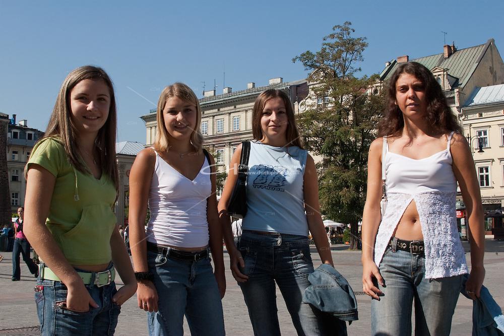 Polish girls chatting together in Rynek Glowny Market square in Krakow Poland