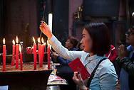 A woman lighting an incense stick with red candles in the Jade Emperor Pagoda, Ho Chi MInh City, Vietnam