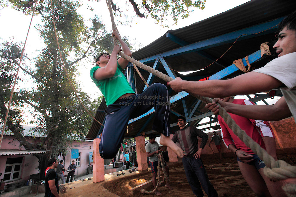 Wrestlers climb the rope attached to the branch of a large tree. For almost 3000 years loincloth clad duels on mud have transfixed spectators across India. Yet wrestling in India is a sport in transition. In 2004 the Indian Fighters Federation tried to prohibit the practice of traditional mud wrestling, claiming that for India to compete at an international level fighters must train using mats. Whilst competing on mud can earn good money for a wrestler at events called dungals in India's countryside, the techniques are starkly different. ..The Guru Hanuman Akhara, a wrestling school in Old Delhi, is the epicentre of this ancient wrestling tradition as it begins to enter the modern world. Now training fighters on both mats and mud the school has produced hundreds of champions at both domestic and international level...Established in 1925, making it the oldest in India, it was in 1955 that Vijay Pal, or Guru Hanuman as he later became known, took over the coaching...Born to a poor family in the desert state of Rajasthan he chose never to marry and instead dedicated his whole life to wrestling, becoming a legend, who created a model for modern Indian wrestling by combining traditional Indian wrestling called Kushti with international standards. His statue and mausoleum stands overlooking the outer courtyard of the school.....