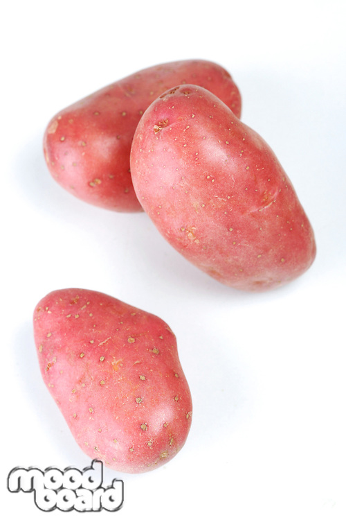 Three red potatoes on white background