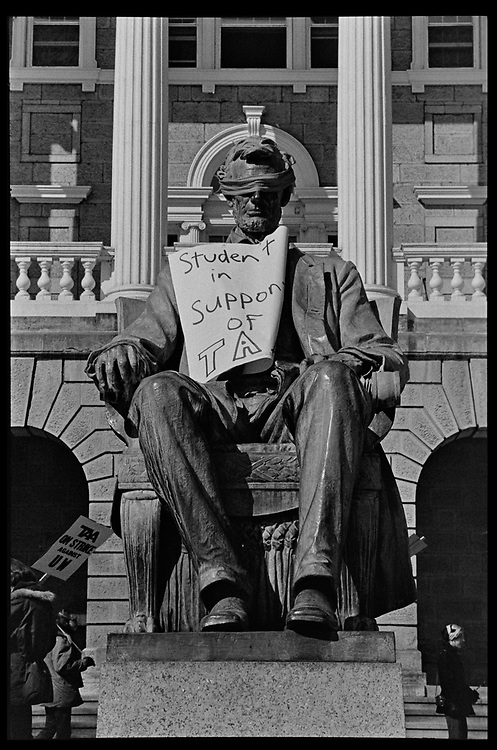 "Madison, WI - March 1970. On March 15, 1970, the University of Wisconsin - Madison Teaching Assistants' Association voted to strike, and the campus was filled with picket lines as well as demonstrations of related and other issues. The strike lasted until early April, when the Association and University came to an agreement. The statue of Abraham Lincoln in front of Bascom Hall wears a blindfold and a sign that reads ""Student in support of TA[A]"""