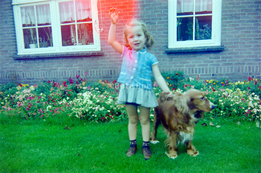young girl posing with dog in the garden Holland late 1960s