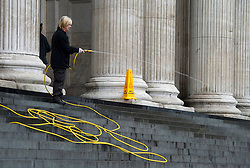 Occupy London Demonstration.As the row escalates over the occupation of the site adjacent to St Paul's by protestors a church employee washes the steps ready for the cathedral to open again. PHOTO BY i-IMAGES