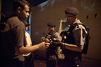 Police Pacification Unit (UPP) officer XXX Pinheiro, and her patrol group, check ID's in Complexo do Caju, a complex of a newly pacified favelas in the North Zone, Rio de Janeiro, Brazil, on Saturday, April 27, 2013. <br />
