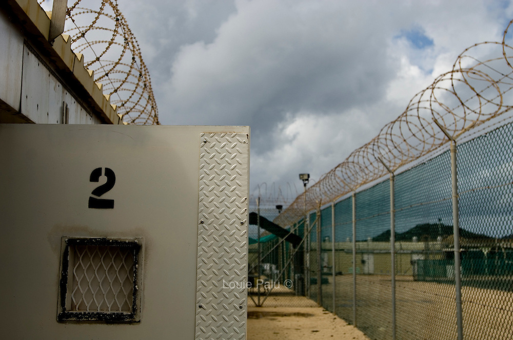 "A cell door and fences lined with razor wire in Camp Four at the Guantanamo Bay detention facility. This is a communal style camp where the most compliant detainees live. According to the military the detainees living in this camp enjoy a more open-air community-style living area where they sleep and eat in small groups. The U.S. Government is currently holding approximately 340 ""enemy combatants"" in Guantanamo Bay, Cuba. They were captured during the ""Global War on Terrorism"" after the attacks on the United States on September 11, 2001. This photo was reviewed by a U.S. Military official before transmission."