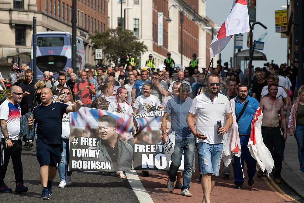 © Licensed to London News Pictures. 01/06/2018. Leeds, UK. Supporters of EDL founder Tommy Robinson ( real name Stephen Yaxley-Lennon ) run through streets in Leeds City Centre and clash with police during a demonstration , after Robinson was convicted of Contempt of Court . Robinson was already serving a suspended sentence for Contempt of Court over a similar incident , when he was convicted on Friday 25th May 2018 . Reporting restrictions , since lifted , initially prevented coverage of Robinson's arrest and incarceration . Photo credit: Joel Goodman/LNP