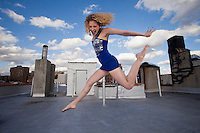 Woman in Blue on Rooftop. Sexy 30's woman jumps for joy on an urban rooftop.