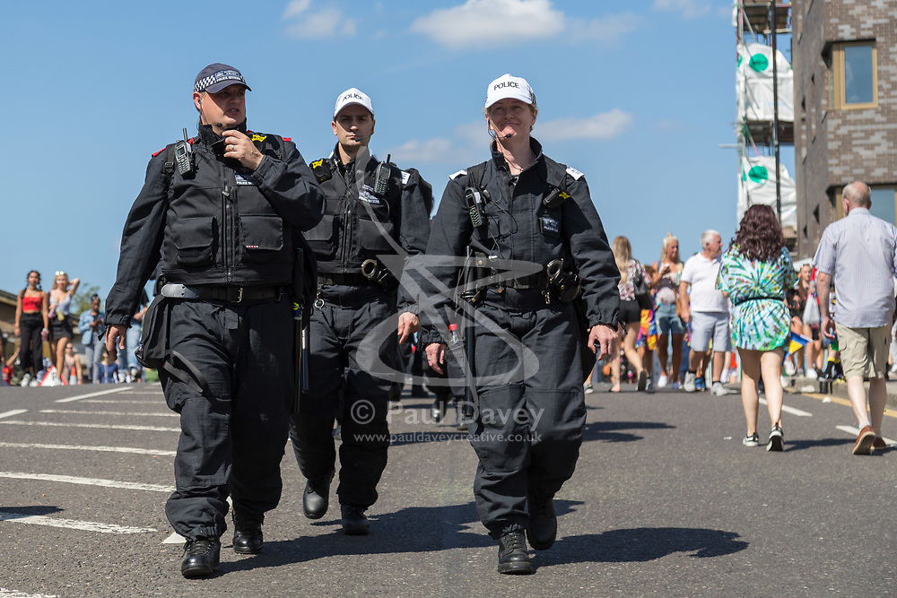 London, August 27 2017. Police make their way towards Ladbroke Grove as Family Day of the Notting Hill Carnival gets underway. The Notting Hill Carnival is Europe's biggest street party held over two days of the bank holiday weekend, attracting over a million people. © Paul Davey.