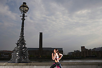 Triathlon athlete running along river embankment London England side view