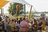 Nederland, Nijmegen, 20160715.<br /> De Kaaij. Cultureel Terras De Kaaij is een gratis festival aan de haven onder de Nijmeegse Waalbrug.<br /> Met veel eettentjes, oa. Taste the Culture dat gerund wordt door Syrische asielzoekers. Gezellig op de Waal strandjes genieten van een drankje en een hapje onder het genot van optredens.<br /> <br /> Netherlands, Nijmegen<br /> The Kaaij. The Cultural Terrace Kaaij is a free festival at the port under the Nijmegen Waal bridge.<br /> With many food stalls, among othersTaste the Culture, run by Syrian fugitives, and many performances. Relaxing on the Waal beaches to enjoy a drink and a snack while enjoying performances.