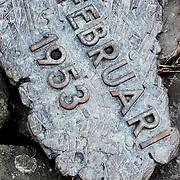 """Nederland Nieuwerkerk aan den Ijssel 2 november 2008 20081102 Foto: David Rozing ..Herdenkingsmonument """" Een dubbeltje op zijn kant """" op de Groenendijk.  Monument ter herdenking aan de watersnoodramp 1 februari 1953. Een dijkdoorbraak van Schielands Hoge Zeedijk bij Nieuwerkerk aan den IJssel werd tenauwernood voorkomen. Het water van de IJssel stond net onder de kruin van de Groenedijk. Nieuwerkerk en het achterliggende gebied werd gespaar omdat Schipper Evergroen op last van de burgemeester zijn schip in de dijk voer en zo het gat dichtte. Het monument beeld het schip en een persoon die zandzakken op het schip legt uit. Als de dijk was bezweken was het volgende gebied ondergelopen: tot Alphen aan den Rijn, Leiden,  Den Haag .  ..Tekst informatiebord bij monument: .""""Dubbeltje op zijn kant"""" herinnert aan de watersnoodramp van 1 februari 1953..Om 0.00 uur was het bij laagwater al NAP +2,60 m. Dit was meer dan de hoogste hoogwaterstand toen bekend. De noordwesterstorm nam toe tot orkaansterkte. De aanhoudende regen, hagel en natte sneeuw verzwakten de dijk. Met man en macht werden zandzakken aangedragen. Behalve de dijkbewaking werkten zo'n 100 mariniers mee. Bij NAP +3,00 m startten de voorbereidingen voor de evacuatie. Zo'n 3 miljoen mensen in het achterland werden bedreigd..Om 4.00 uur werd NAP +3,84 m bereikt en spoelde er water over de onverharde dijk. Het water sloeg de binnenzijde stuk. Op sommige plaatsen was de dijk nog maar 1 meter breed!.Om 5.30 uur sloeg er een gat van 15 meter in de dijk! Er moest iets gebeuren. Burgemeester J.C. Vogelaar van Nieuwerkerk aan den IJssel vorderde het schip de Twee Gebroeders van A. Evegroen, dat in de buurt lag. De schipper zette de 'kop' van zijn schip in de dijk en zwenkte de achtersteven naar het gat. Als een sluisdeur sloot de Twee Gebroeders het gat. Daarna werd het met zandzakken gevuld. Toen de dijk bij Ouderkerk aan den IJssel doorbrak zakte de waterstand en nam de waterdruk af...Het monument is van het Hoogheemraad"""