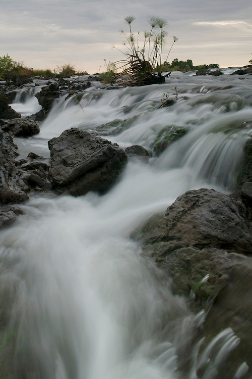 Africa, Namibia, The Okavango River flows over Popa Falls at dusk in the Caprivi Strip