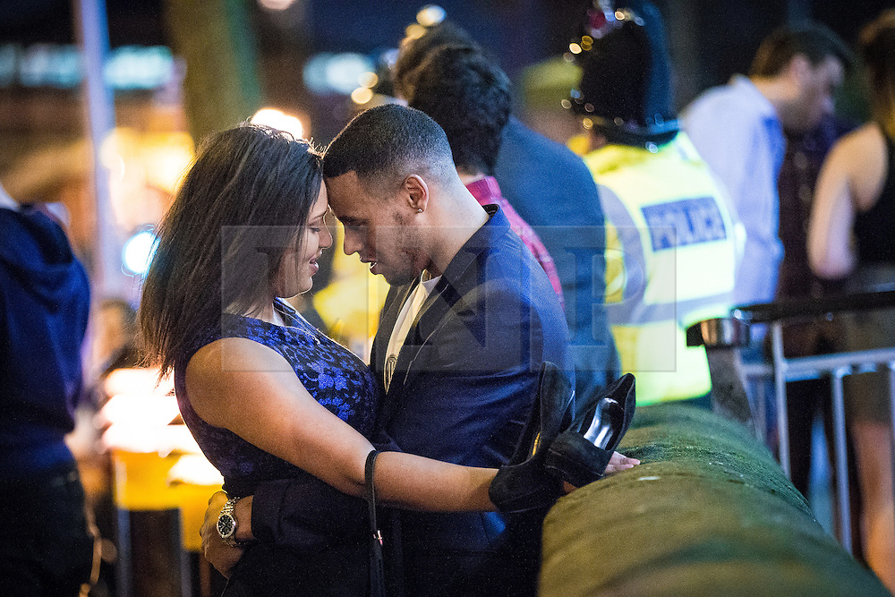 "© Licensed to London News Pictures . 19/12/2015 . Manchester , UK . An amorous couple . Revellers in Manchester enjoy "" Mad Friday "" - also known as "" Black Eye Friday "" - the day on which emergency services in Britain are typically at their busiest , as people head out for parties and drinks to celebrate Christmas . Photo credit : Joel Goodman/LNP"