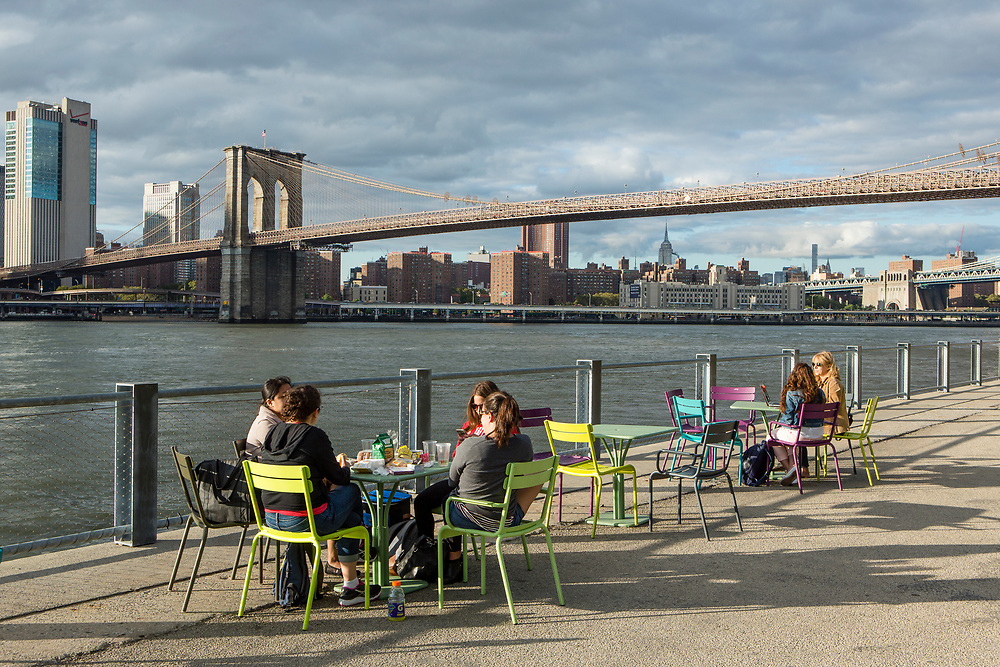 Brooklyn, NY - 9 September 2017. People relax in the late afternoon by the East River in Brooklyn Bridge Park.