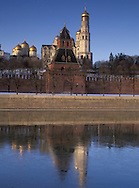 The Kremlin Wall, golden cupolas of the<br /> Kremlin churches and the banks of the partially<br /> frozen Moskva River, Moscow, Russia