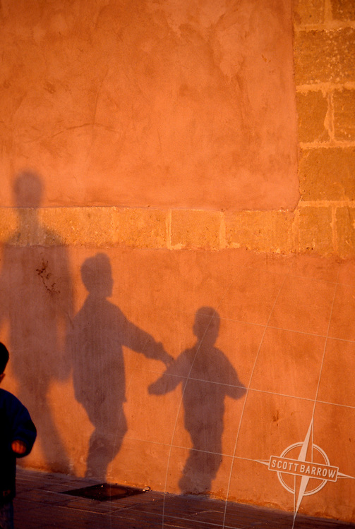 Silhouettes on a wall of people passing by.