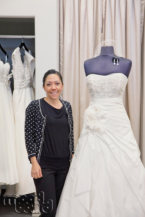 Portrait of a mature employee standing by elegant wedding dress in bridal store