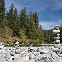 Rock cairns on the Smith River riverbed at Jebediah Smith Redwoods State Park in Northern California, USA.