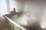 Looking over a batch of wort as steam rises and is exposed to bacteria in the coolship room. (Photo @ Andy Manis)