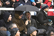 Fans attempt to cover up from the rain during the EFL Sky Bet Championship match between Fulham and Burton Albion at Craven Cottage, London, England on 20 January 2018. Photo by Richard Holmes.