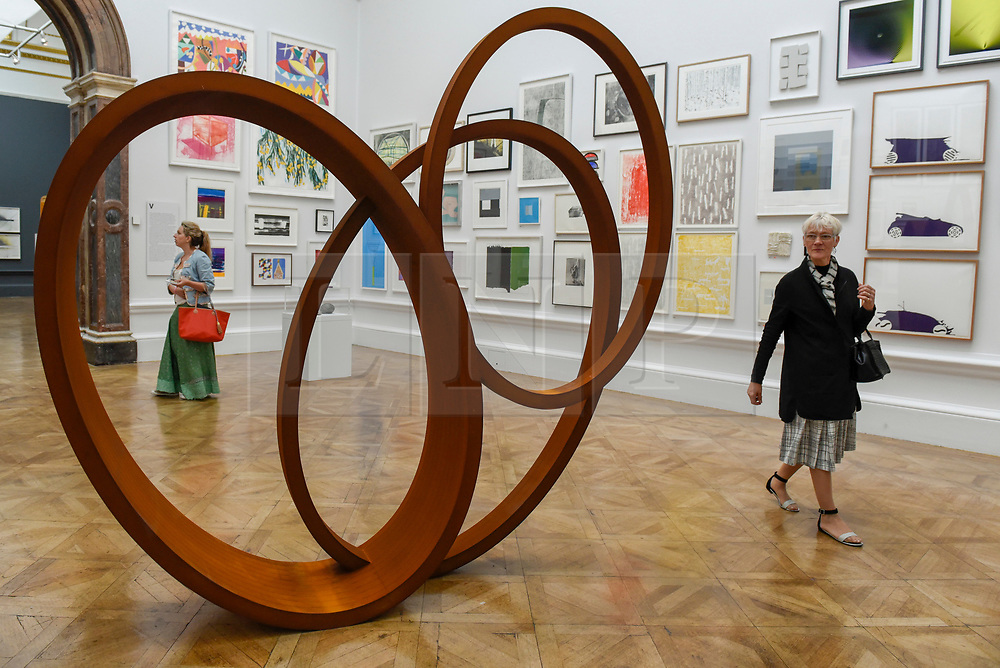 """© Licensed to London News Pictures. 08/06/2017. London, UK. A visitor passes by a scuplture called """"Natural Pearl"""" by Nigel Hall RA (GBP189,600).  Preview of the Summer Exhibition 2017 at the Royal Academy of Arts in Piccadilly.  Co-ordinated by Royal Academician Eileen Cooper, the 249th Summer Exhibition is the world's largest open submission exhibition with around 1,100 works on display by high profile and up and coming artists.<br />  Photo credit : Stephen Chung/LNP"""