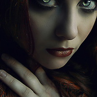 Close upon a young woman with green eyes and red hair in a dark setting staring intensely at the camera