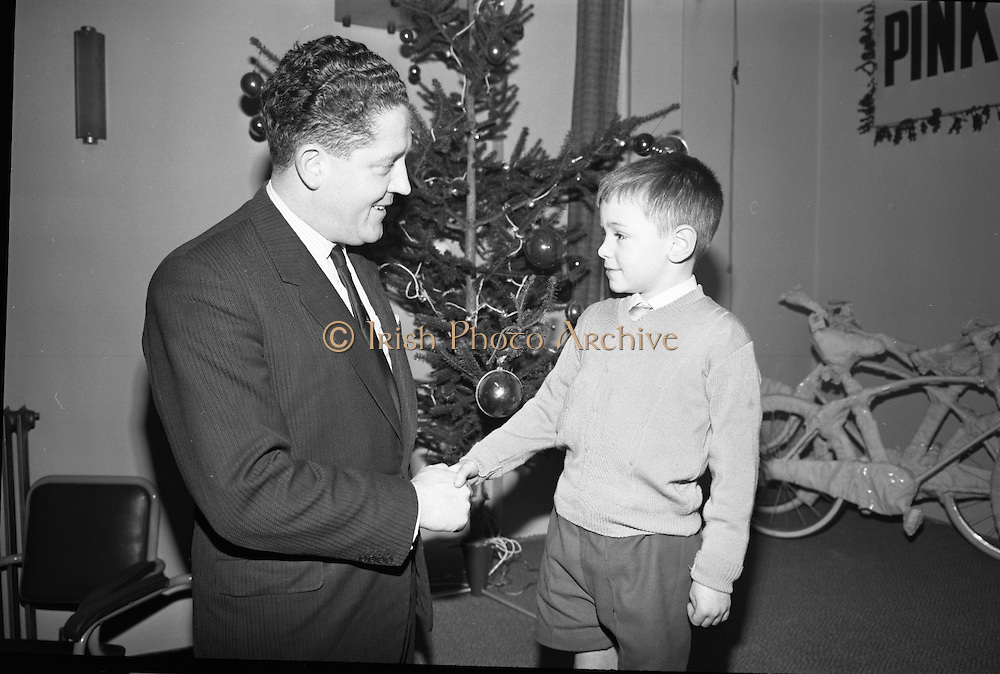 """Presentations at Shell and BP, Fleet Street..1964..18.12.1964..12.18.1964..18th December 1964..At Shell & BP house in Fleet Street, Dublin, the Minister for Justice, Mr Brian Lenihan TD was on hand to present prizes to young winners in """"The Pink Paraffin""""competition...Image shows The Minister for Justice, Mr Brian Lenihan TD, congratulating a young prizewinner at the prize giving ceremony. Unfortunately we do not have the childs name, if you know her/him why not let us know at irishphotoarchive@gmail.com."""