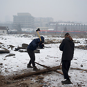 Two Afghan migrants chop wood near an abandon train wagon in central Belgrade. Some migrants opt to take over disused barracks and wagons left abandoned near Belgrade's main railway station.