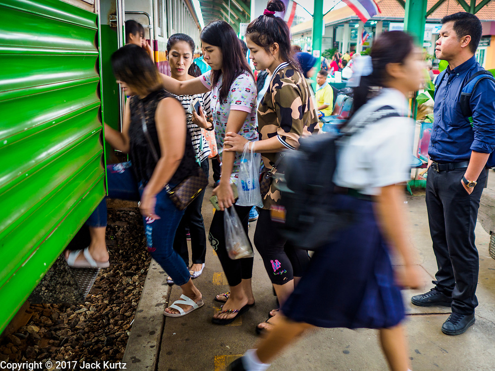 31 MAY 2017 - CHACHOENGSAO, THAILAND: Bangkok bound passenger line up to a board a train while a local high school student disembarks at the train station in Chachoengsao, a provincial town about 50 miles and about an hour by train from Bangkok. The train from Chachoengsao to Bangkok takes a little over an hour but traffic on the roads is so bad that the same drive can take two to three hours. Thousands of Thais live outside of Bangkok and commute into the city for work on trains, busses and boats.       PHOTO BY JACK KURTZ