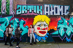 © Licensed to London News Pictures. 11/02/2020. London, UK. Women share a joke as they walk past graffiti depicting Prime minister Boris Johnson as a clown, near Brick Lane in London. Photo credit: Vickie Flores/LNP