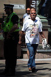 """© Licensed to London News Pictures . 07/07/2018 . Leeds , UK . A man wearing a """" Free Tommy Robinson t-shirt """" at an anti-Islam demonstration by supporters of jailed EDL founder Tommy Robinson , including those from the """" Yorkshire Patriots """" and """" First for Britain """" , in Leeds City Centre , opposed by anti-fascists . Robinson ( real name Stephen Yaxley-Lennon ) was convicted of Contempt of Court in May 2018 after committing a second offence , whilst serving a suspended sentence for the same crime . Photo credit : Joel Goodman/LNP"""