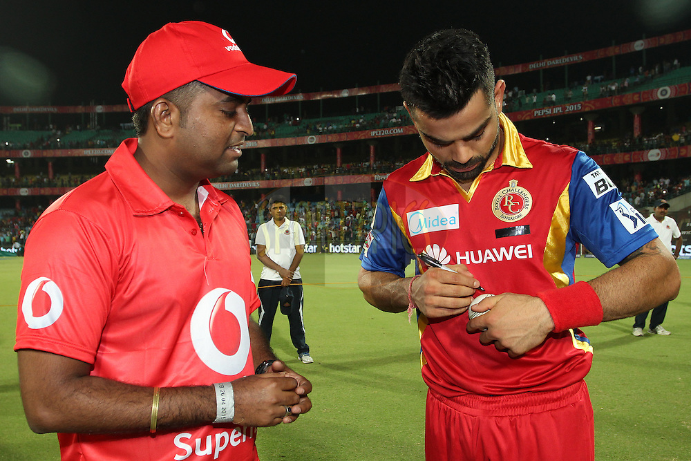 The Vodafone Superfan looks on as Royal Challengers Bangalore captain Virat Kohli signs the Match Ball during match 26 of the Pepsi IPL 2015 (Indian Premier League) between The Delhi Daredevils and The Royal Challengers Bangalore held at the Ferozeshah Kotla stadium in Delhi, India on the 26th April 2015.<br /> <br /> Photo by:  Shaun Roy / SPORTZPICS / IPL