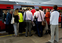 File photo dated 28/07/2016 of commuters waiting to board a train as first class train carriages will be cut on busy suburban routes to stop commuters being crammed into packed carriages, Chris Grayling has said.