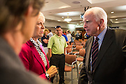 23 AUGUST 2012 - PEORIA, AZ:  Senator JOHN McCAIN (R-AZ), talks a supporters after a town hall meeting in Peoria, AZ. Sen. McCain held a town hall in Peoria, a suburb of Phoenix, to talk about the impact that sequestration would have on the Arizona economy and the Department of Defense. McCain said sequestration would immediately cost Arizona more than 35,000 defence related jobs and decimate the armed forces. Sequestration would result in about $1.2 trillion being cut from the federal budget. Sequestration, and automatic budget cuts, is scheduled to go into effect on Jan 1, 2013, if the President and Congress can't agree on budget.     PHOTO BY JACK KURTZ