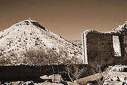 """A hill peak with a cross is viewed through the empty window of a building ruin in far West Texas in sepia tone. NOTE: Click """"Shopping Cart"""" icon for available sizes and prices. If a """"Purchase this image"""" screen opens, click arrow on it. Doing so does not constitute making a purchase. To purchase, additional steps are required."""