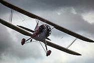 Clients are taking scenic biplanes rides in light rain in the 1942 Waco UPF-7 of TacAero.