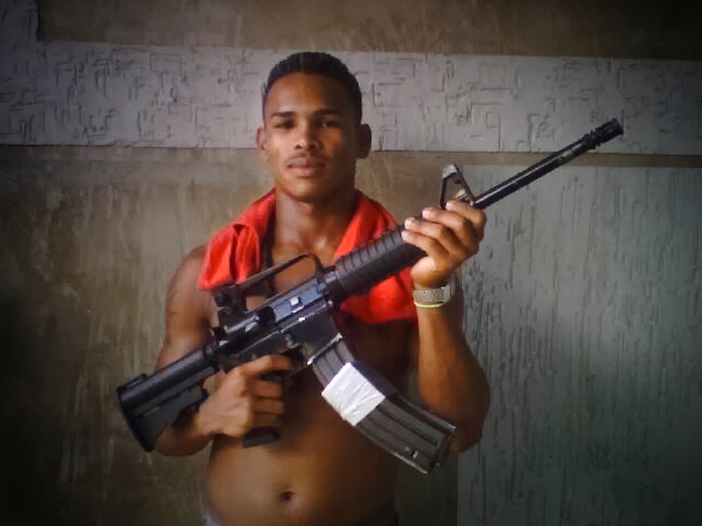 "**IMAGE PROVIDED BY A PRISONER WHO WISHES TO REMAIN ANONYMOUS, PLEASE CREDIT ACCORDINGLY**  One of Teófilo Rodríguez's bodyguards poses for a portrait with the weapon he carries inside San Antonio prison in Porlamar, Venezuela. "" There's enough guns and ammunition here to start a war,"" said prisoner Paul Makin, 33, ""handguns, machine guns, AK-47s, AR-15s, M-16s, magnums, colts, Berettas, Uzis, Mac 10, Ingram's...You name them, it's in here."""
