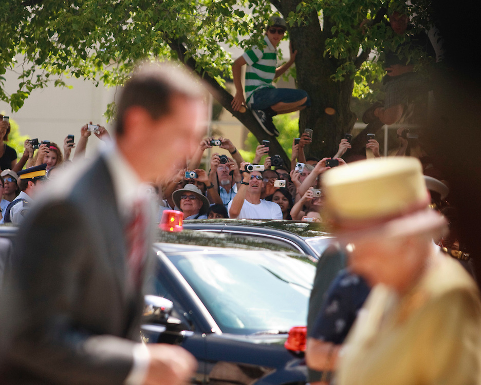 Hundreds of onlookies strain to get a picture or a glimpse of Queen Elizabeth II as she is greated by Ontario Premier Dalton McGuinty outside of Research in Motion where she toured the facilities of the Blackberry maker in Waterloo, Ontario, July 5, 2010.<br /> AFP/GEOFF ROBINS/STR