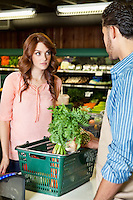 Beautiful young woman looking at store clerk in supermarket