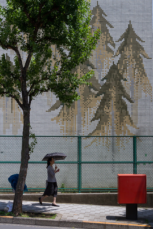 A Japanese woman uses a parasol as she walks under s shade tree next to an apartment building wall decorated with a mosaic  forests Hanzomon, Tokyo, Japan. Thursday June 13th 2019