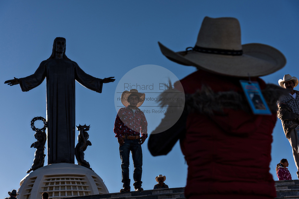 Mexican cowboys are silhouetted as they take photos at the statue of Cristo Rey on the top of Cubilete Mountain during the annual Cabalgata de Cristo Rey pilgrimage January 6, 2017 in Guanajuato, Mexico. Thousands of Mexican cowboys and horse take part in the three-day ride to the mountaintop shrine of Christo Rey.