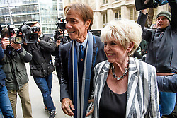 © Licensed to London News Pictures. 13/04/2018. London, UK. SIR CLIFF RICHARD arrives at the Rolls Building of the High Court in London with television presenter GLORIA HUNNIFORD, where he is claiming damages against the BBC for loss of earnings. The 77-year-old singer is suing the corporation after his home in Sunningdale, Berkshire was raided following allegations of sexual assault made to Metropolitan Police. Photo credit: Ben Cawthra/LNP