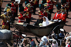 Prince Harry and Meghan Markle ride in an open-topped carriage through Windsor Castle after their wedding in St George's Chapel.