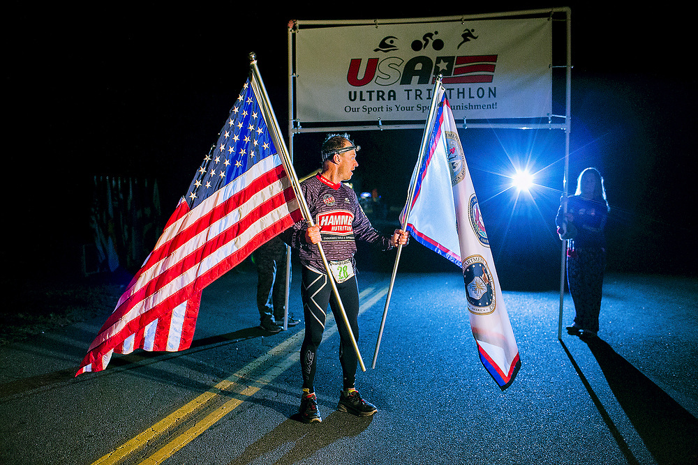 SPOTSYLVANIA, VA - OCTOBER 14, 2016:  Adolphus Dolph Hoch IV  holds the American flag at the finish line after winning the 1x5 competition on the fifth day of the Quintuple Anvil race in Lake Anna State Park in Spotsylvania, Virginia. CREDIT: Sam Hodgson for The New York Times.