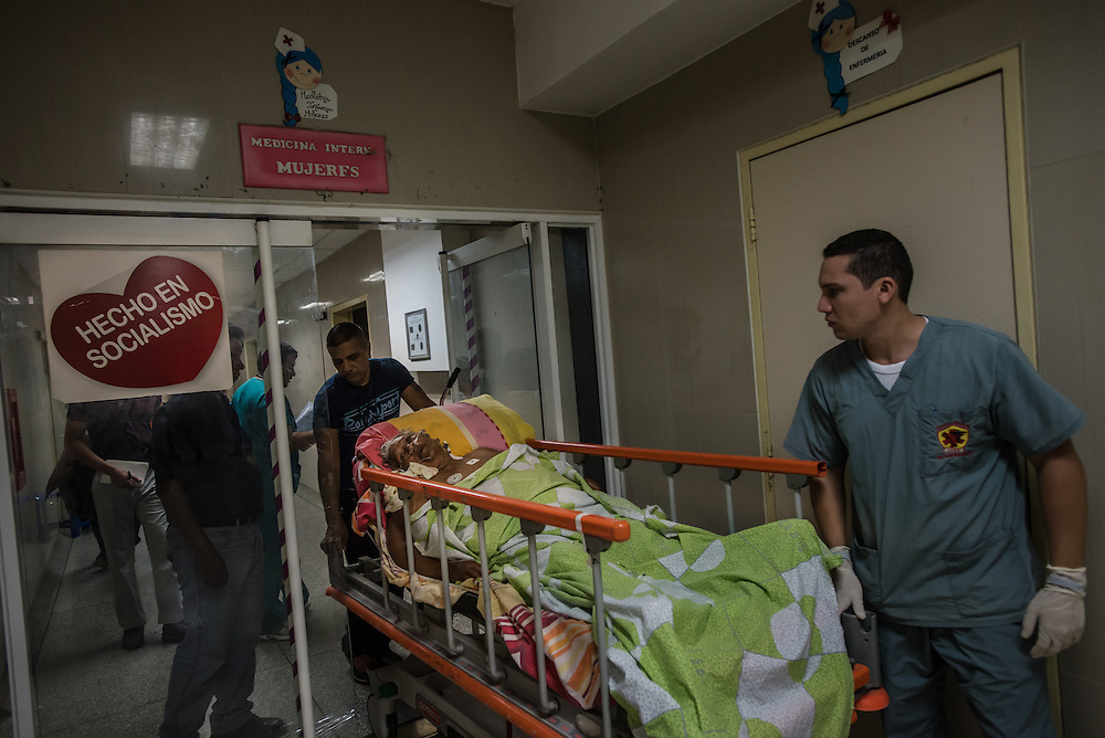 "PUERTO LA CRUZ, VENEZUELA - APRIL 15, 2016: Hospital staff move Rosa Parucho, a diabetic patient in septic shock from an upper floor of the hospital to the emergency room, through a door that has a sign with a large red heart, that says in Spanish, ""Made in Socialism"". Doctors were limited in how they could care for her, because they don't have a dialysis machine, nor the antibiotics that she requires. Ms. Parucho contracted an infection while in the hospital, that spread to her feet, which had now turned black and doctors said require amputation.  Hospital Universitario Dr. Luís Razetti is one of the worst state-run, public hospitals in Venezuela.  Doctors compare it to working in a war zone - they regularly have to turn patients away, because they don't have the majority of medicines  or medical equipment and supplies needed to give them medical attention.  When they do accept patients, they have to work with extremely limited resources, because they don't have the supplies they need for things like X-Rays,  and many exams nd operations.  The hospital's infrastructure is crumbling, and staff don't have all the cleaning supplies required to keep the hospital sanitary. The hospital also suffers from weekly shortages of running water and electricity.  In April, several babies died when a power outage turned off the incubators, and the hospital's generator failed to work because of lack of maintenance.  The same month, authorities found over 100 pieces of medical equipment, stolen from the hospital in the home of the assistant to the hospital's director.  Despite having the largest oil reserves in the world, falling oil prices and wide-spread government corruption have pushed Venezuela into an economic crisis, with the highest inflation in the world and chronic shortages of food and medical supplies. PHOTO: Meridith Kohut"