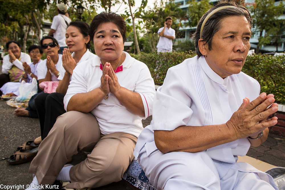 26 JANUARY 2013 - BANGKOK, THAILAND:  Thai Buddhists pray during a mass pilgrimage of monks in Bangkok Saturday. 1,128 Buddhist monks from the Dhammakaya movement took part in a 25-day pilgrimage walk passing through Bangkok and several provinces in central Thailand, as part of a voluntarily undertaking of ascetic practices. The pilgrimage is scheduled to end Sunday, January 27 at Wat Phra Dhammakaya near Bangkok. Along the way Thai Buddhists laid marigolds along their path and greeted them for merit making. The Dhammakaya is the fastest growing Buddhist movement in Thailand. The pilgrimage is reported to be the largest pilgrimage in Thailand and organizers hope to get it placed in the Guiness World Records book.     PHOTO BY JACK KURTZ