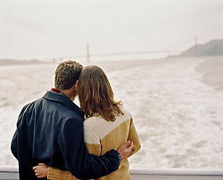 Back of a couple on a boat looking at the Golden Gate Bridge