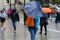 © Licensed to London News Pictures. 07/10/2019. London, UK. A woman struggles to control an umbrella on a wet and windy afternoon in Trafalgar Square. Photo credit: Dinendra Haria/LNP