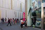 With a giant David Beckham towering over them in the Westfield mall, spectators pause before entering the Olympic Park during the London 2012 Olympics, the 30th Olympiad. Situated on the fringe of the 2012 Olympic park, Westfield is Europe's largest urban shopping centre providing the main access to the Olympic park with a central 'street' giving 75% of Olympic visitors access to the main stadium so retail space..